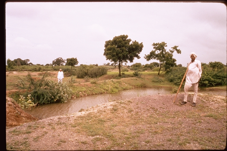 Man stands next to small rainwater harvesting pond in India. Photo: International Rivers on Flickr.