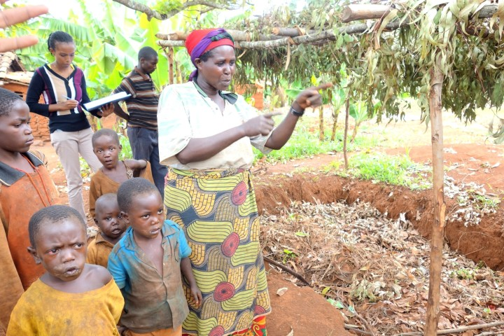 a farmer showing us her compost pit